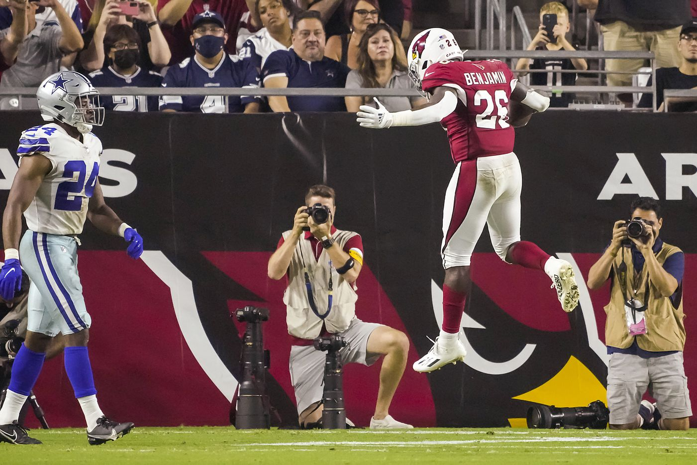 Arizona Cardinals running back Eno Benjamin (26) leaps into the end zone with a touchdown  past Dallas Cowboys cornerback Kelvin Joseph (24) during the second quarter of an NFL football game at State Farm Stadium on Friday, Aug. 13, 2021, in Glendale, Ariz.