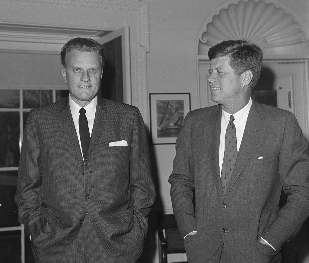 On Dec. 12, 1961, evangelist Billy Graham talks with President John F. Kennedy during a call at the the White House in Washington.   Graham, who transformed American religious life through his preaching and activism, becoming a counselor to presidents and the most widely heard Christian evangelist in history, has died. Spokesman Mark DeMoss says Graham, who long suffered from cancer, pneumonia and other ailments, died at his home in North Carolina on Wednesday, Feb. 21, 2018. He was 99.