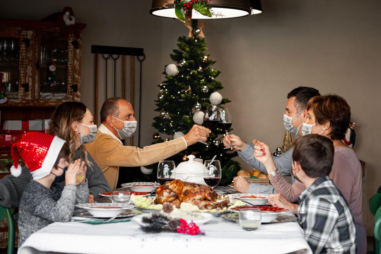 Una familia con mascarillas se reúnen para celebrar la navidad.
