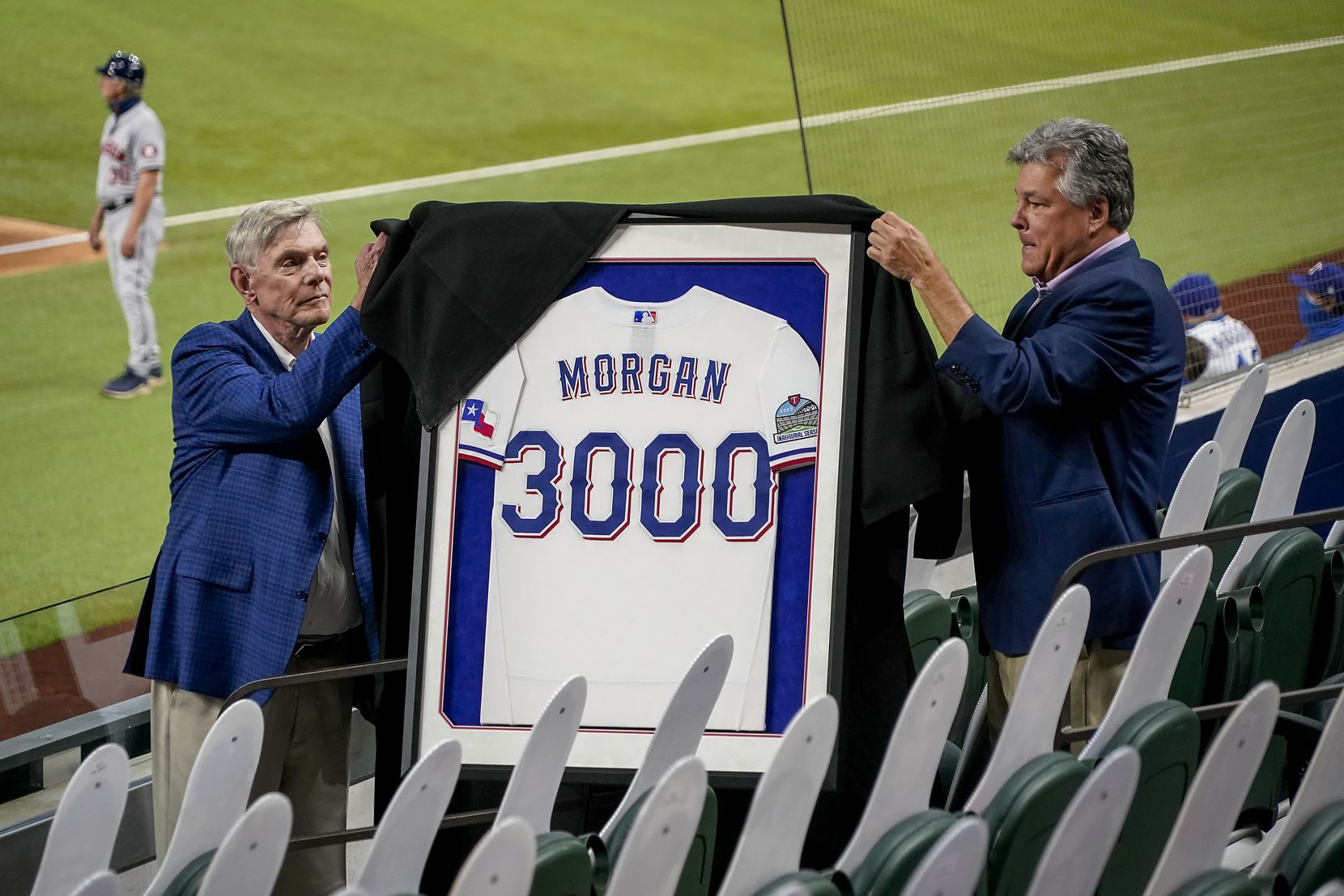 Texas Rangers co-chairman and managing partner Ray C. Davis (left) and chairman, ownership committee and chief operating officer Neil Leibman unveil a framed jersey commemorating public address announcer Chuck Morgan's 3000th consecutive game after the fifth inning between the Texas Rangers and the Houston Astros at Globe Life Field on Saturday, Sept. 26, 2020.