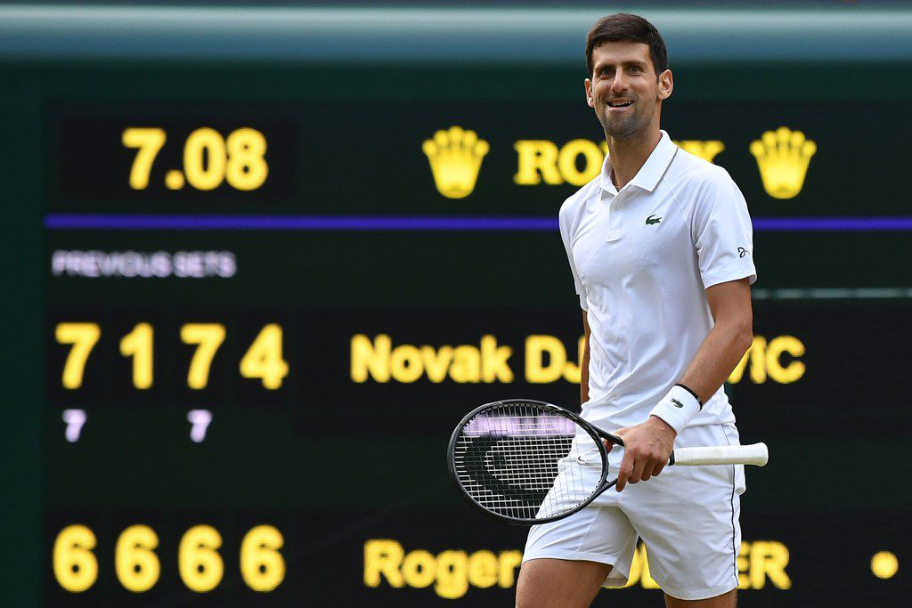 Serbia's Novak Djokovic celebrates beating Switzerland's Roger Federer during their men's singles final on day thirteen of the 2019 Wimbledon Championships at The All England Lawn Tennis Club in Wimbledon, southwest London, on July 14, 2019. (Photo by Ben STANSALL / AFP) / RESTRICTED TO EDITORIAL USEBEN STANSALL/AFP/Getty Images