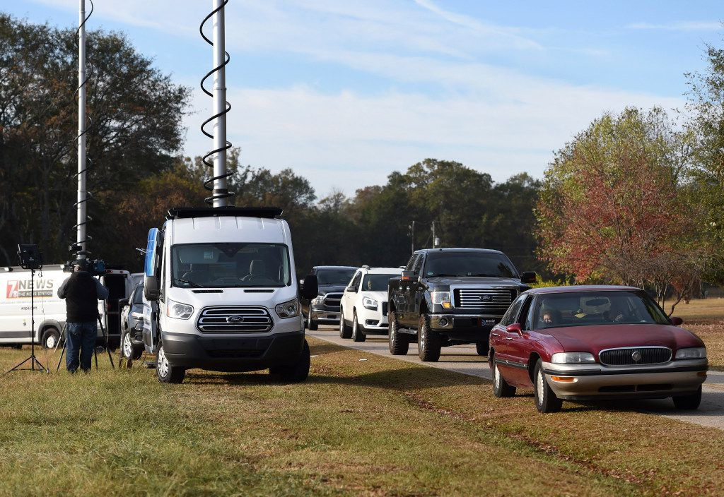 People drive and look while media sets up at Todd Kohlhepp's property in Woodruff, S.C. Sunday, Nov. 6, 2016. Kohlhepp, accused of holding a woman chained inside a storage container, was due in court for a bond hearing Sunday after investigators say he confessed to an unsolved quadruple murder that happened 13 years ago. He's also charged with the woman's kidnapping, and prosecutors say more charges are expected. (AP Photo/Richard Shiro)