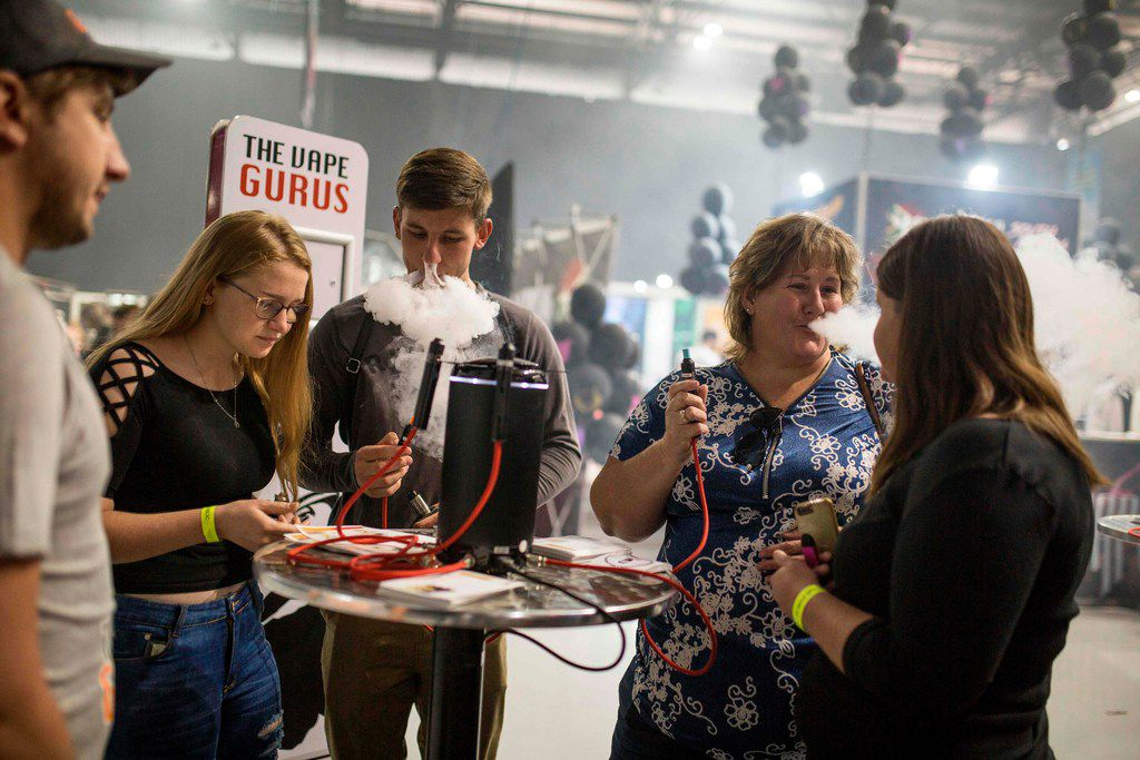 People try different electronic cigarettes on stands during VapeCon in Pretoria, South Africa, on Sept. 1, 2019. - V