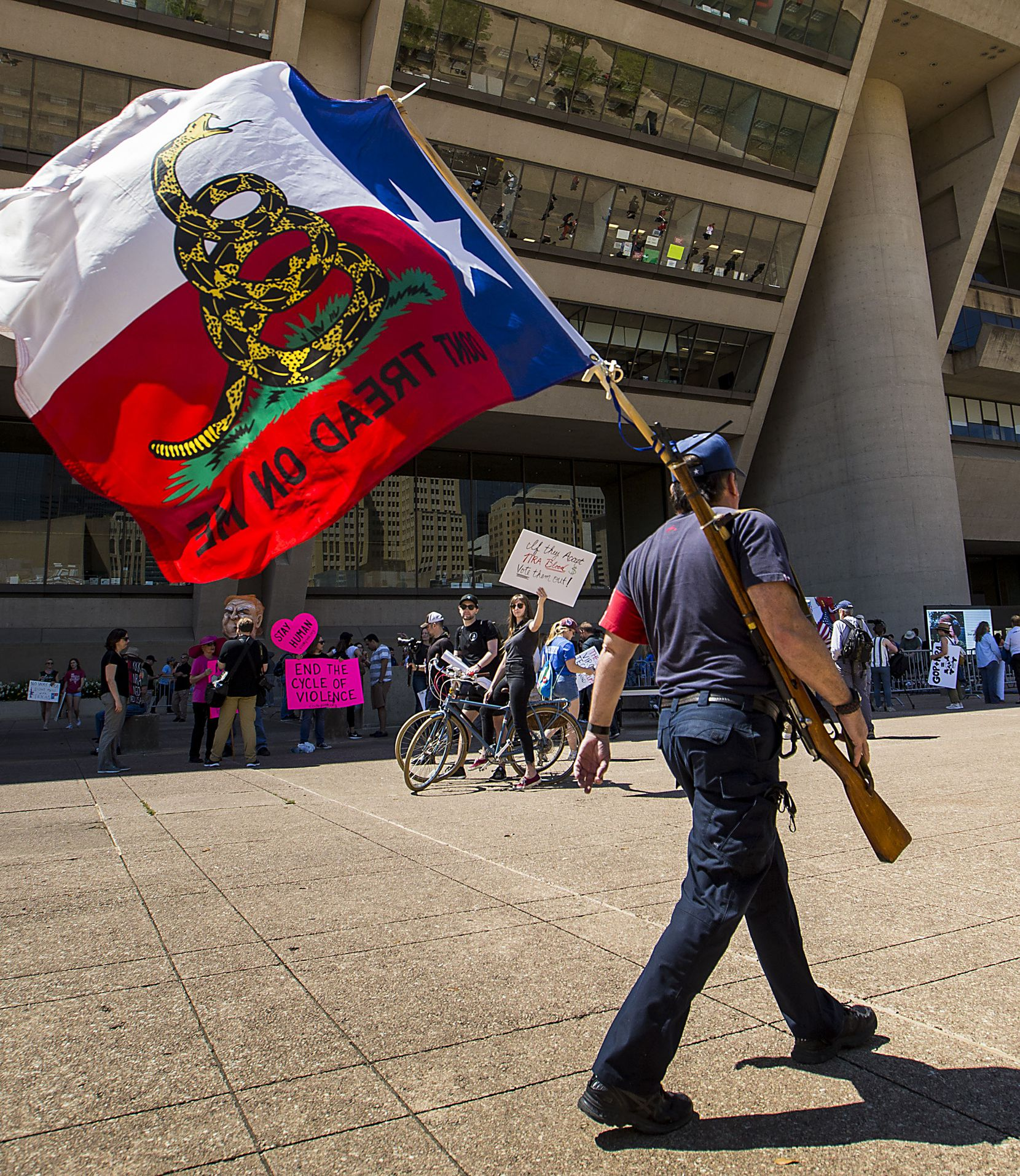 Gun rights advocate Brad McClain carries a rifle and flag as he walks past a rally of gun control advocates outside Dallas City Hall during the NRA Annual Meeting & Exhibits at the Kay Bailey Hutchison Convention Center on Saturday, May 5, 2018, in Dallas.