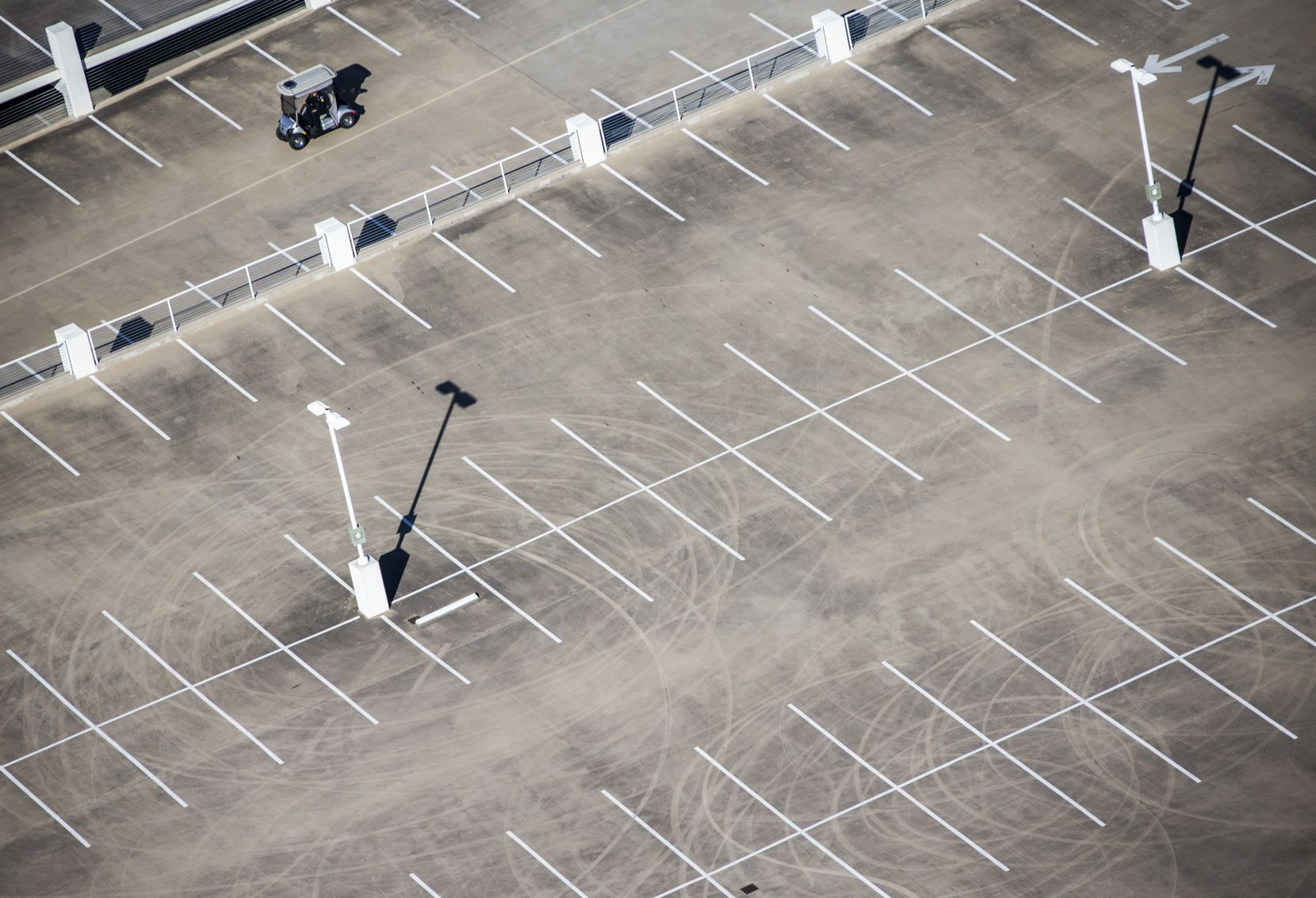 A security guard drives a golf cart past tire marks showing evidence of stunt driving on the top level of a NorthPark parking garage where two men were  struck by a car in March.