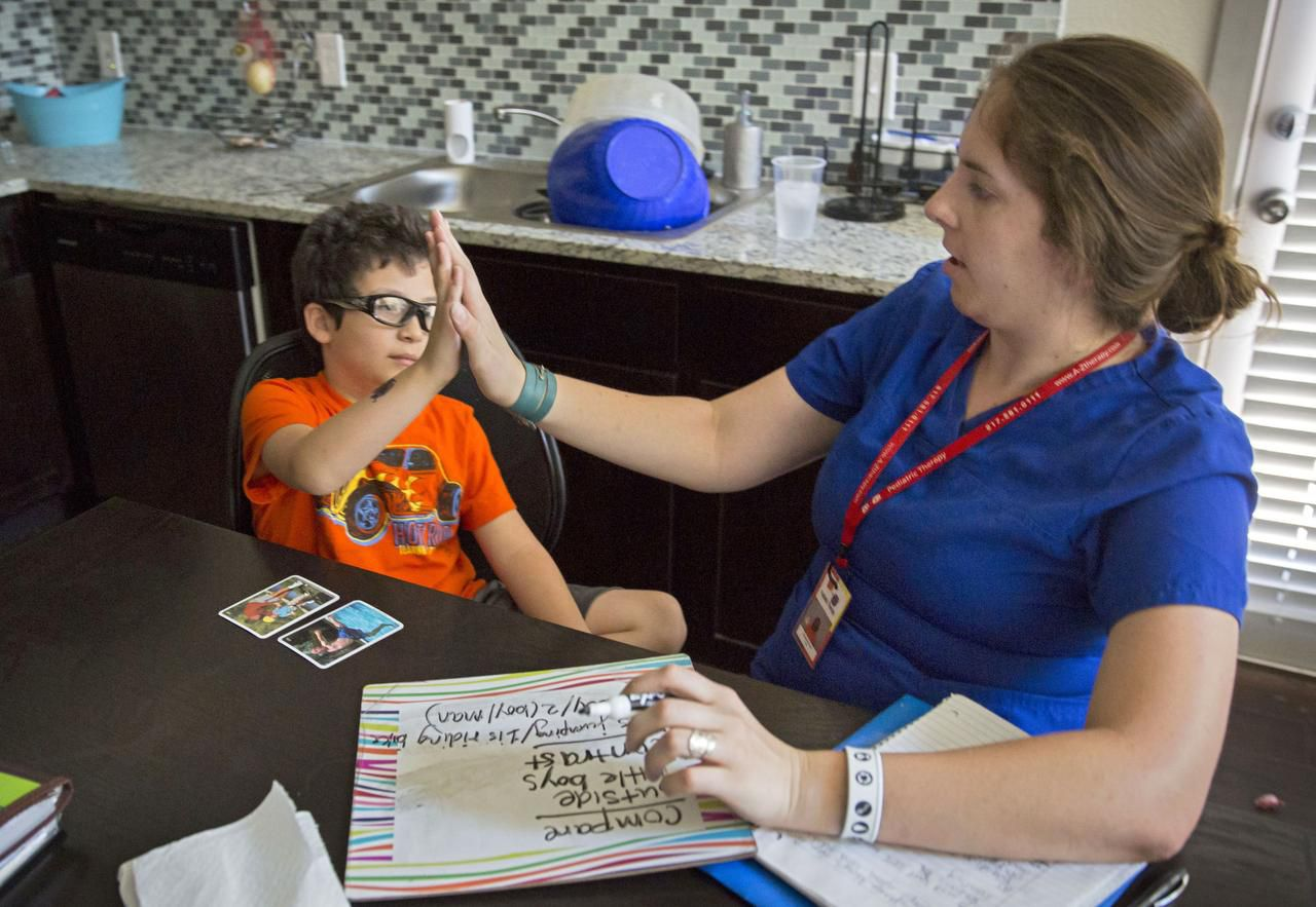 Speech therapist Elizabeth Price works with Jacob Casablanca, who has autism-like symptoms, in Hurst. His mom says home visits are an essential part of his care.