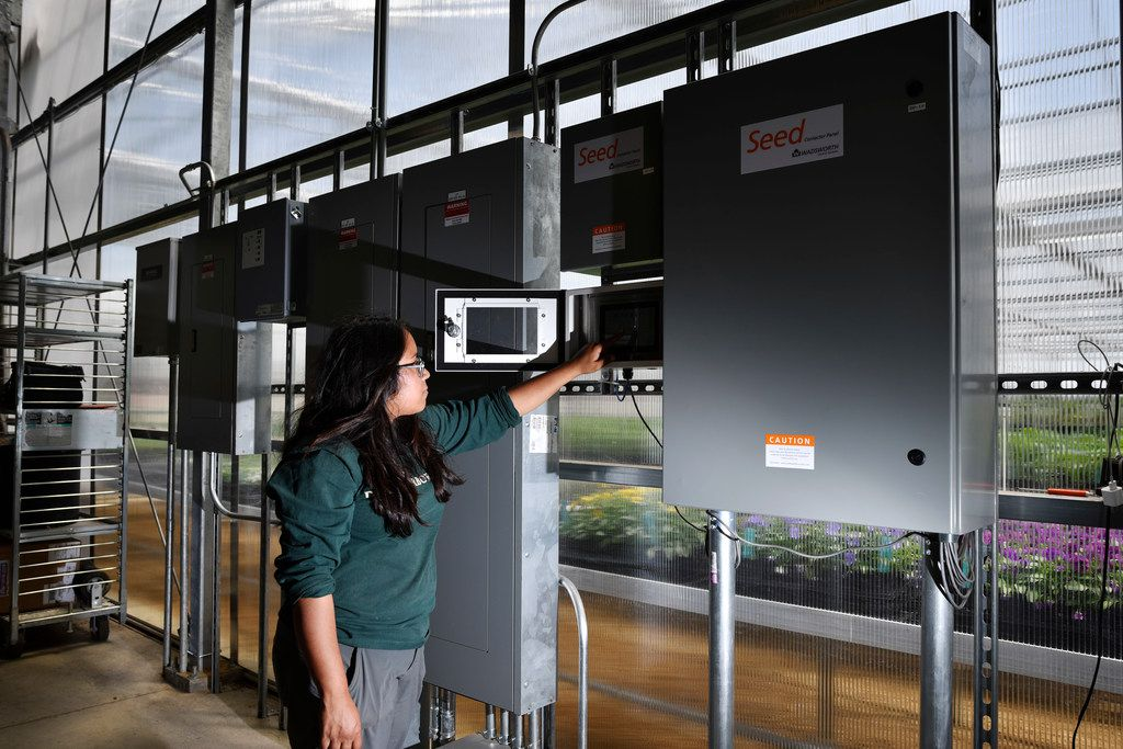 Ana Swinson, the greenhouse manager, shows off the Wadsworth Control Panel at Dallas Arboretum's newest greenhouse, The Tom and Phyllis McCasland Horticulture Center. The panel and system controls and regulates temperatures inside the greenhouse.