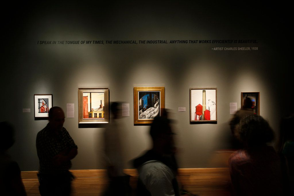 """People walk in front of selected pieces of art during a soft opening of """"Cult of the Machine: Precisionism and American Art"""" at the Dallas Museum of Art in Dallas on Sept. 13, 2018."""