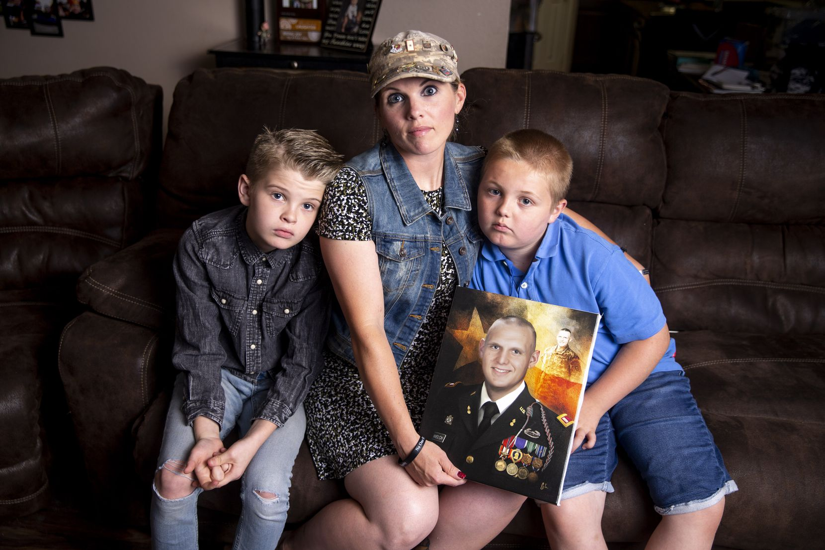 Becky Welch poses with her sons Aaden Welch, 11, left, and Robby Welch, 9, with a portrait of Army 1st Lt. Robert Welch, in their Wylie, Texas home Friday, May 31, 2019.