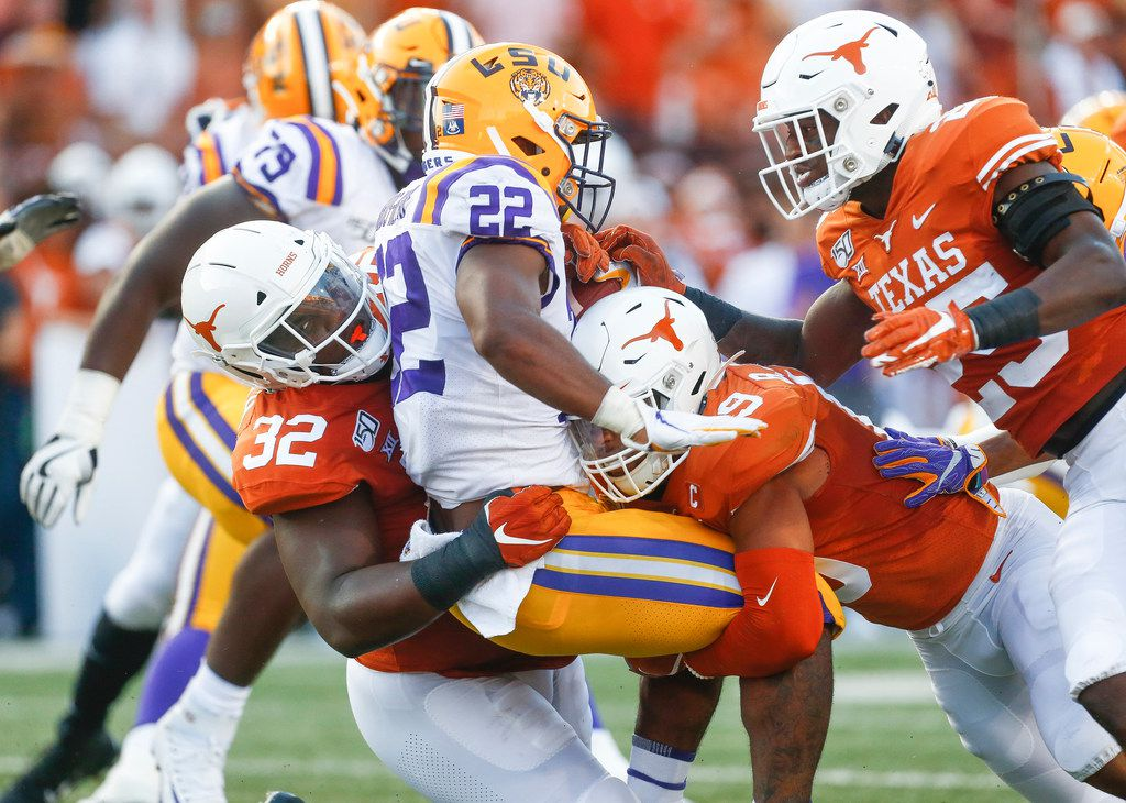 Texas Longhorns defensive lineman Malcolm Roach (32) and defensive back Brandon Jones (19) put a stop to LSU Tigers running back Clyde Edwards-Helaire (22) during the first quarter of a college football game between the University of Texas and Louisiana State University on Saturday, Sept. 7, 2019 at Darrell Royal Memorial Stadium in Austin, Texas. (Ryan Michalesko/The Dallas Morning News)