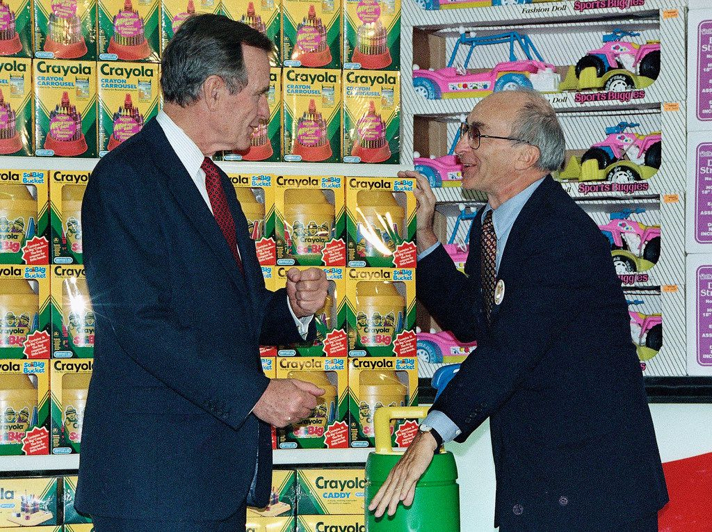 In this Jan. 7, 1992, file photo, President George H. Bush, left, listens to Toys R Us Chairman Charles Lazarus, right, as he visits the toy chain's second store to open in Japan.