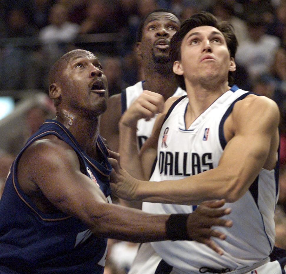 Michael Jordan de los Wizards de Washington y Eduardo Nájera de los Mavericks de Dallas pelean por recuperar un balón en un partido en el American Airlines Center en diciembre de 2001.