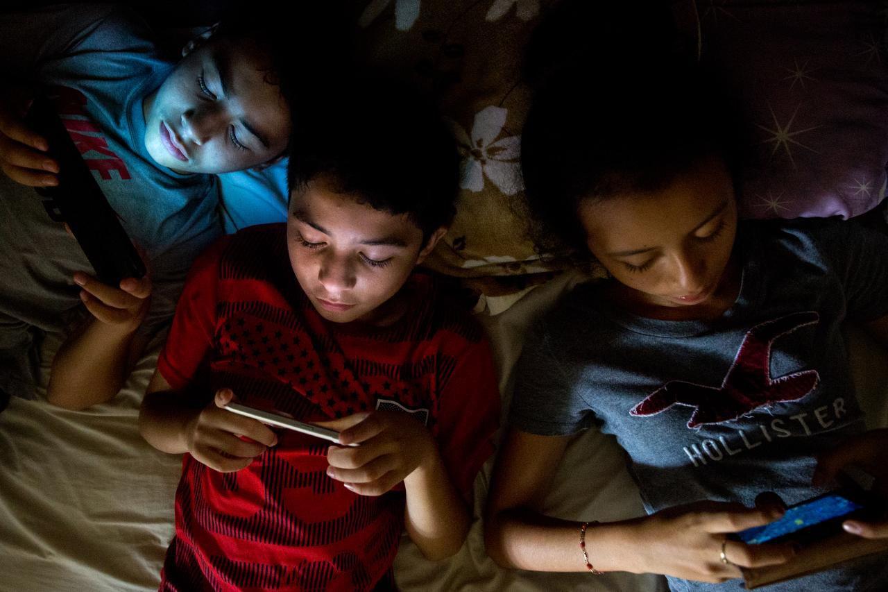 JUAN (centro) y Luis Lara juegan videojuegos con su prima Ena Medina. El Wi-fi es limitado en Hoctún, Yucatán. COURTNEY PEDROZA/DMN