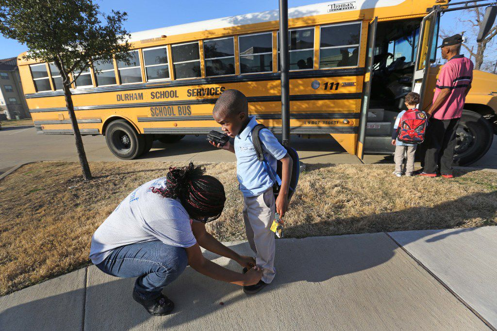 Chanelle Cook ties her son's shoe after he is dropped off at Buckeye Trail Commons by the school bus. Matthew, 6, attends a charter school 10 miles away in Pleasant Grove. (Louis DeLuca/Staff Photographer)