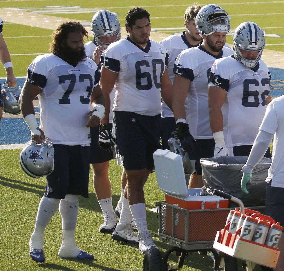 Dallas Cowboys offensive tackle Isaac Alarc—n (60) and Dallas Cowboys center Joe Looney (73) make their way into the on field air conditioned tent during the first day of training camp at Dallas Cowboys headquarters at The Star in Frisco, Texas on Friday, August 14, 2020. (Vernon Bryant/The Dallas Morning News)