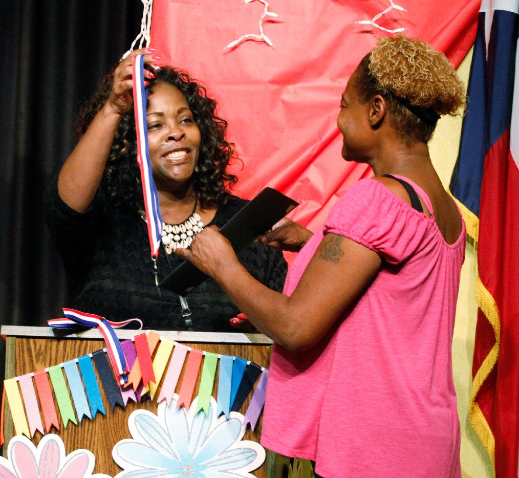 Crystal Thomas, left, school counselor, left, gives Paula Wooten an award for her granddaughter, Râreanna Wooten, 11, at George W. Carver Creative Arts Learning Center in May.