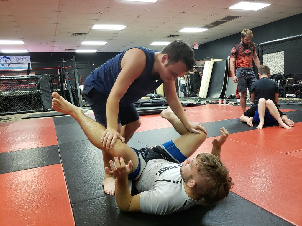 Dylan Miller (top) practices a jiu-jitsu drill on Levi Mowles at Fitness Fight Factory in North Richland Hills, Texas. Devin Miller, a mixed martial arts fighter, holds a special needs class for his brother Dylan and others with autism.