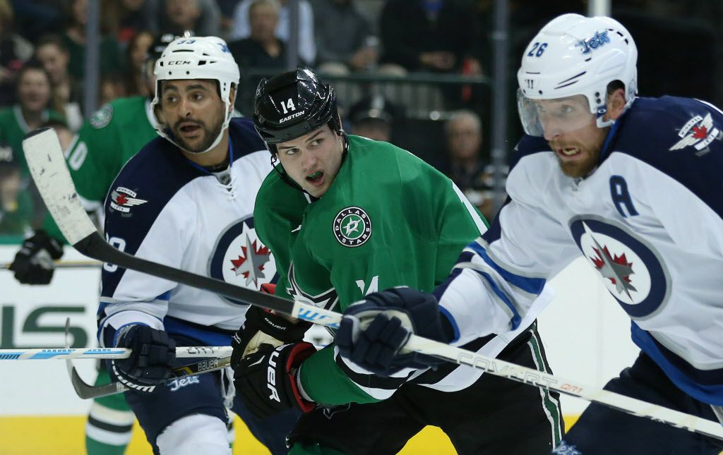 Dallas Stars left wing Jamie Benn (14) attempts to move toward the puck between Winnipeg Jets defenseman Dustin Byfuglien (left) and right wing Blake Wheeler (right) in the first period during a National Hockey League game between the Winnipeg Jets and the Dallas Stars at the American Airlines Center in Dallas Thursday November 12, 2015. (Andy Jacobsohn/The Dallas Morning News)
