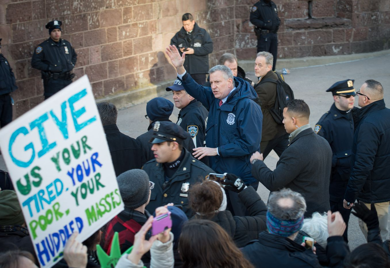 NYC Mayor Bill de Blasio waves as protesters gather in Battery Park and march to the offices of Customs and Border Patrol in Manhattan to protest President Trump's Executive order.