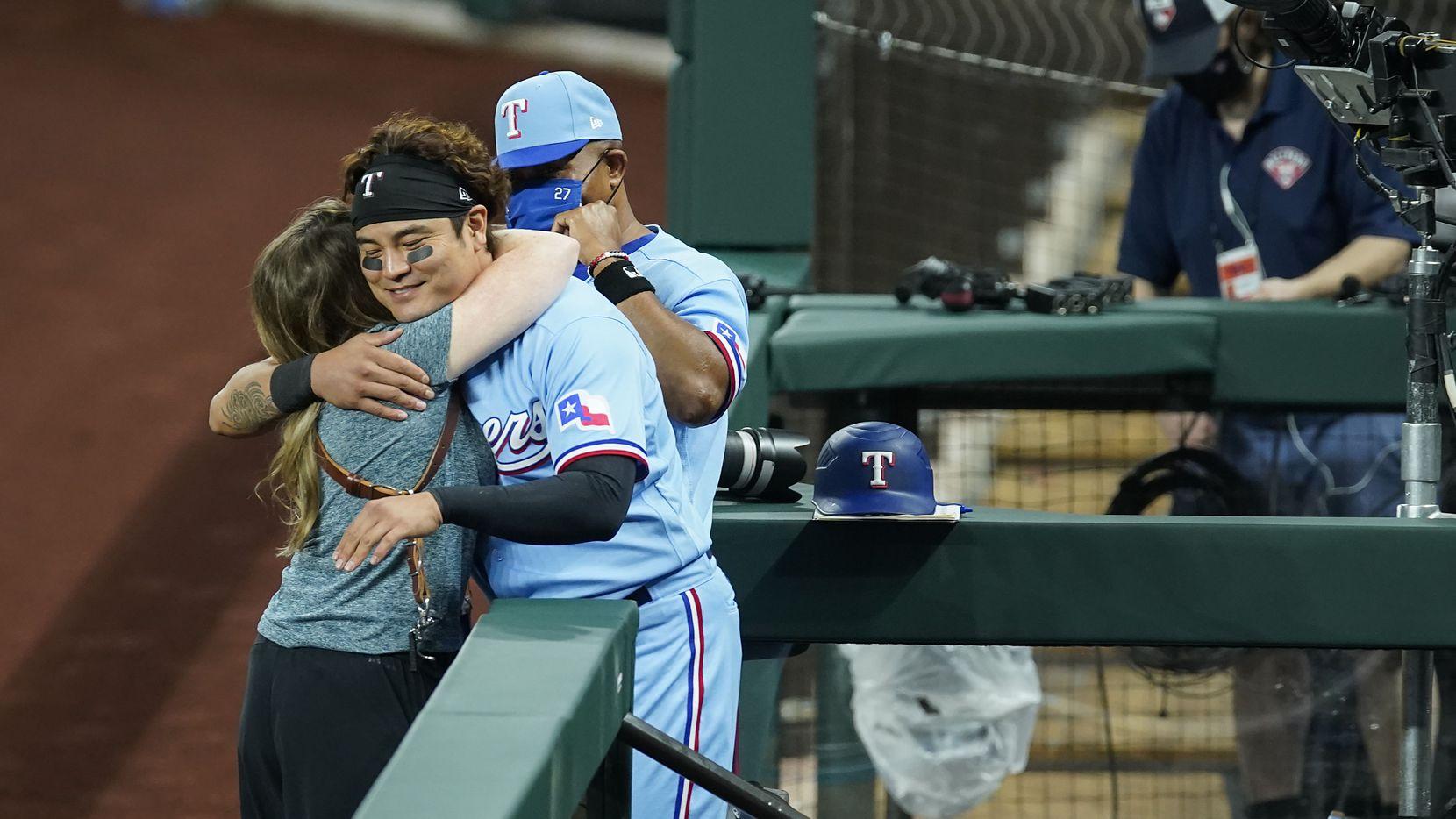 Rangers outfielder/designated hitter Shin-Soo Choo hugs team photographer Kelly Gavin as third base coach Tony Beasley looks on following an 8-4 win over the Astros in the Rangers' season finale at Globe Life Field on Sunday, Sept. 27, 2020.