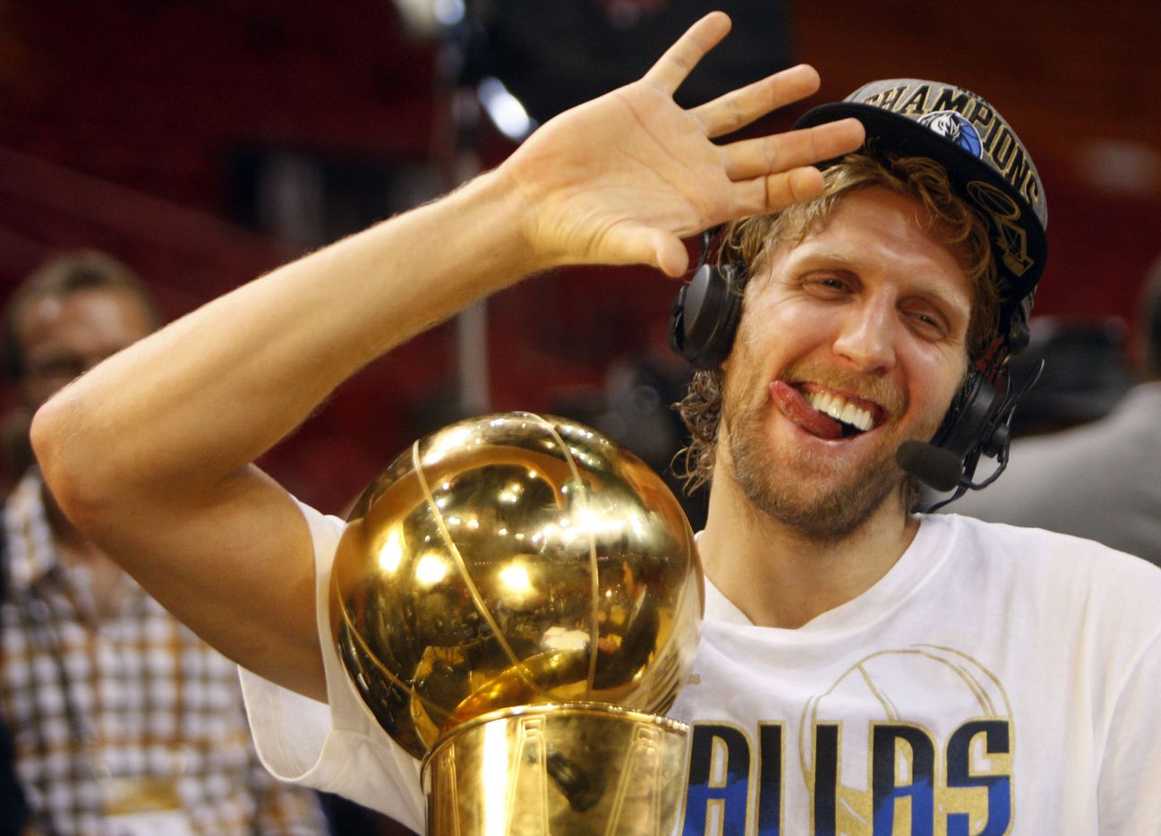 Dallas Mavericks power forward Dirk Nowitzki (41) shows how he drinks his champagne with his right hand after he was asked if he had any problems holding the bottle in celebration after winning in game six of the NBA Finals between the Miami Heat and the Dallas Mavericks at the American Airlines Arena in Miami, Florida, June 12, 2011. The Mavericks won 105-95 to take the title. (Vernon Bryant/The Dallas Morning News) Nowitzki is holding the Larry O'Brien NBA Championship trophy. 06142011xMAVSspecial