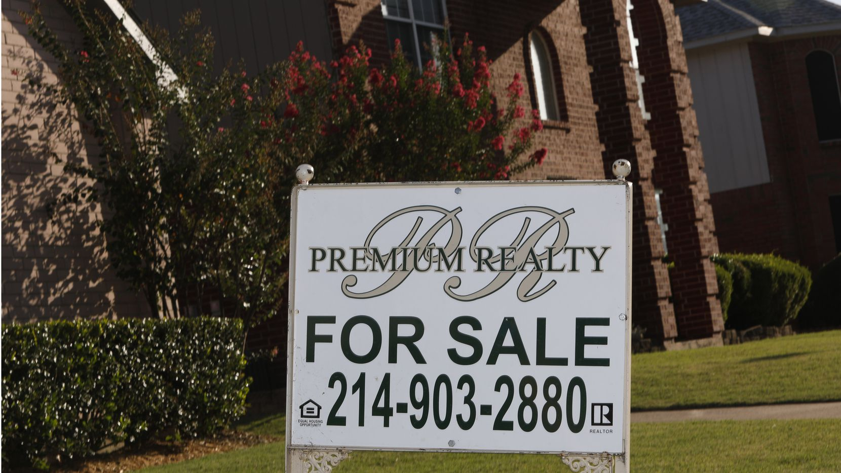 """A """"For Sale"""" sign stands in front of a house on Trees Drive in Cedar Hill, Texas on Monday, August 10, 2020. Home sales in North Texas exploded in July, rising 25% from a year ago to the largest ever single-month sales total."""