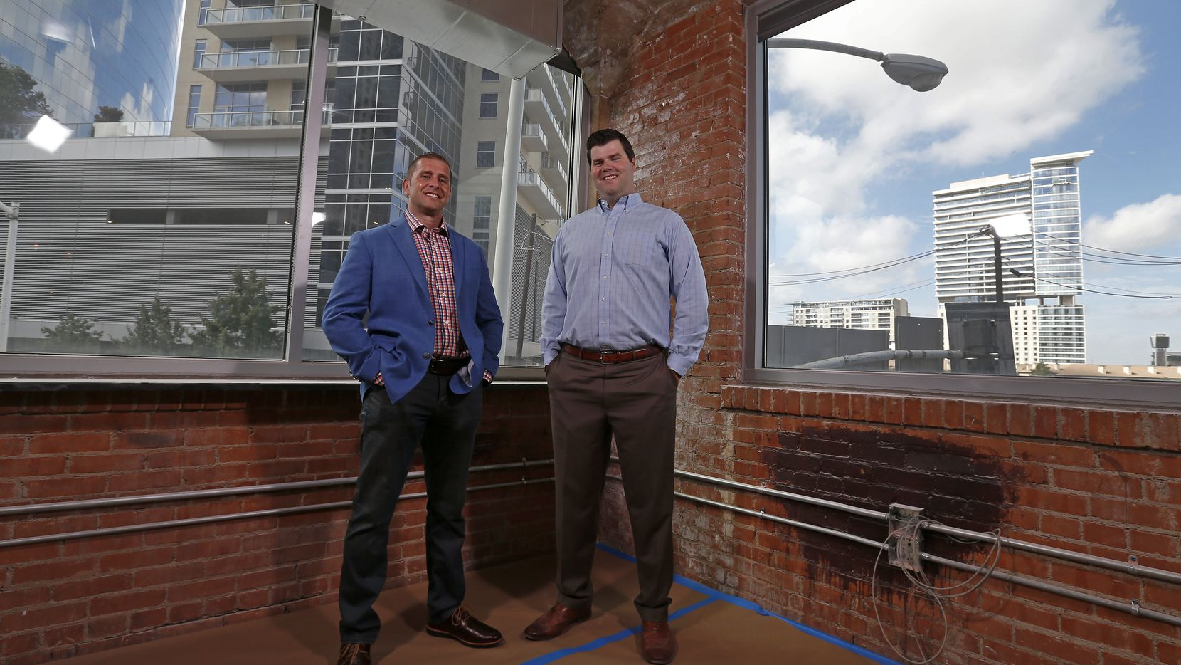 Josh McLeod (left), vice president of Regus, and Brian Bigham, area manager of Regus, pose for a photograph in front of the original wall of the historic furniture company building at the new shared office facility at 1919 McKinney Avenue in Dallas.