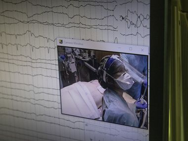 The average cost of a COVID-19 hospitalization is about $20,000, according to a Kaiser Family Foundation report, but Delta Air Lines said it was paying an average of about $50,000 — and the unvaccinated accounted for all recent cases. Here, Dr. Catherine Chen appears on a camera monitor as she reads oxygen levels for a COVID-19 patient at Parkland Memorial Hospital.