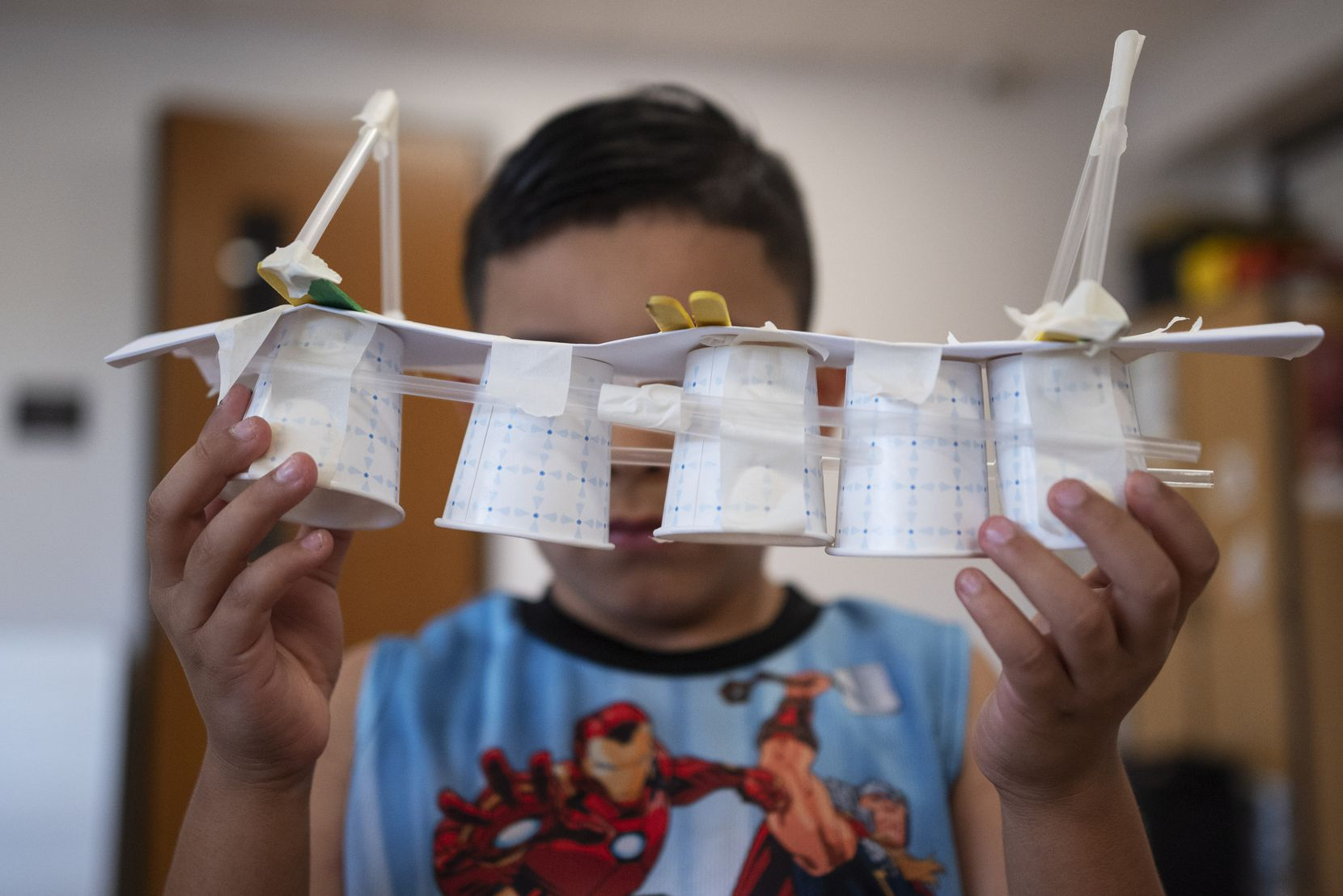 A young boy shows off a bridge he created using a variety of items such as cups, paper and popsicle sticks.
