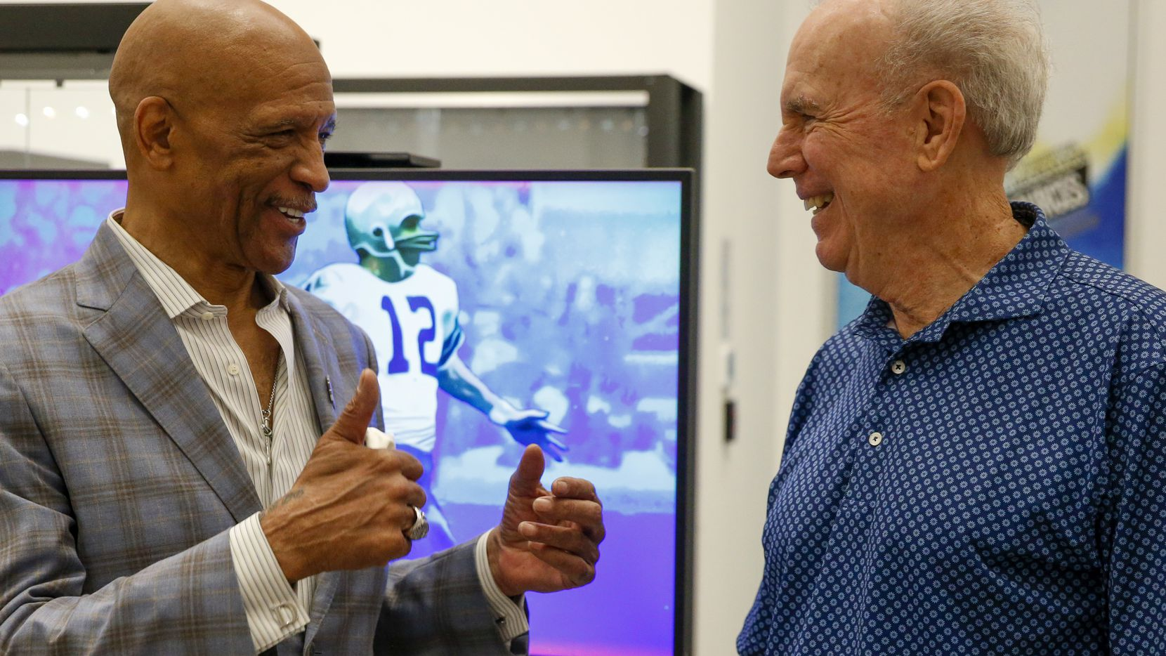 Former Dallas Cowboys players Drew Pearson (left) and Roger Staubach chat at the unveiling of an NFT depicting their famous Hail Mary play from 1975 at Heritage Auctions on Wednesday, July 21, 2021, in Dallas.