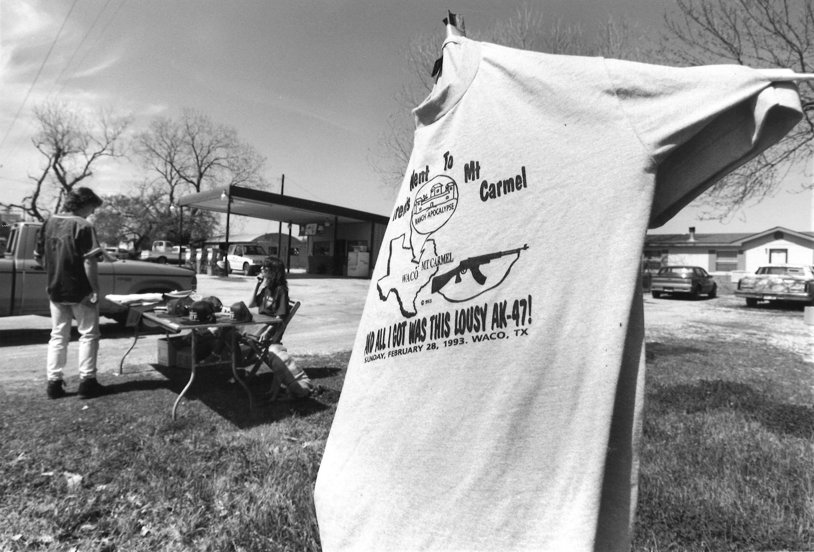 """March 23, 1993: Linda Cox sold T-shirts near the compound, including this shirt reading, """"My parents went to Mt. Carmel and all I got was this lousy AK-47!"""""""