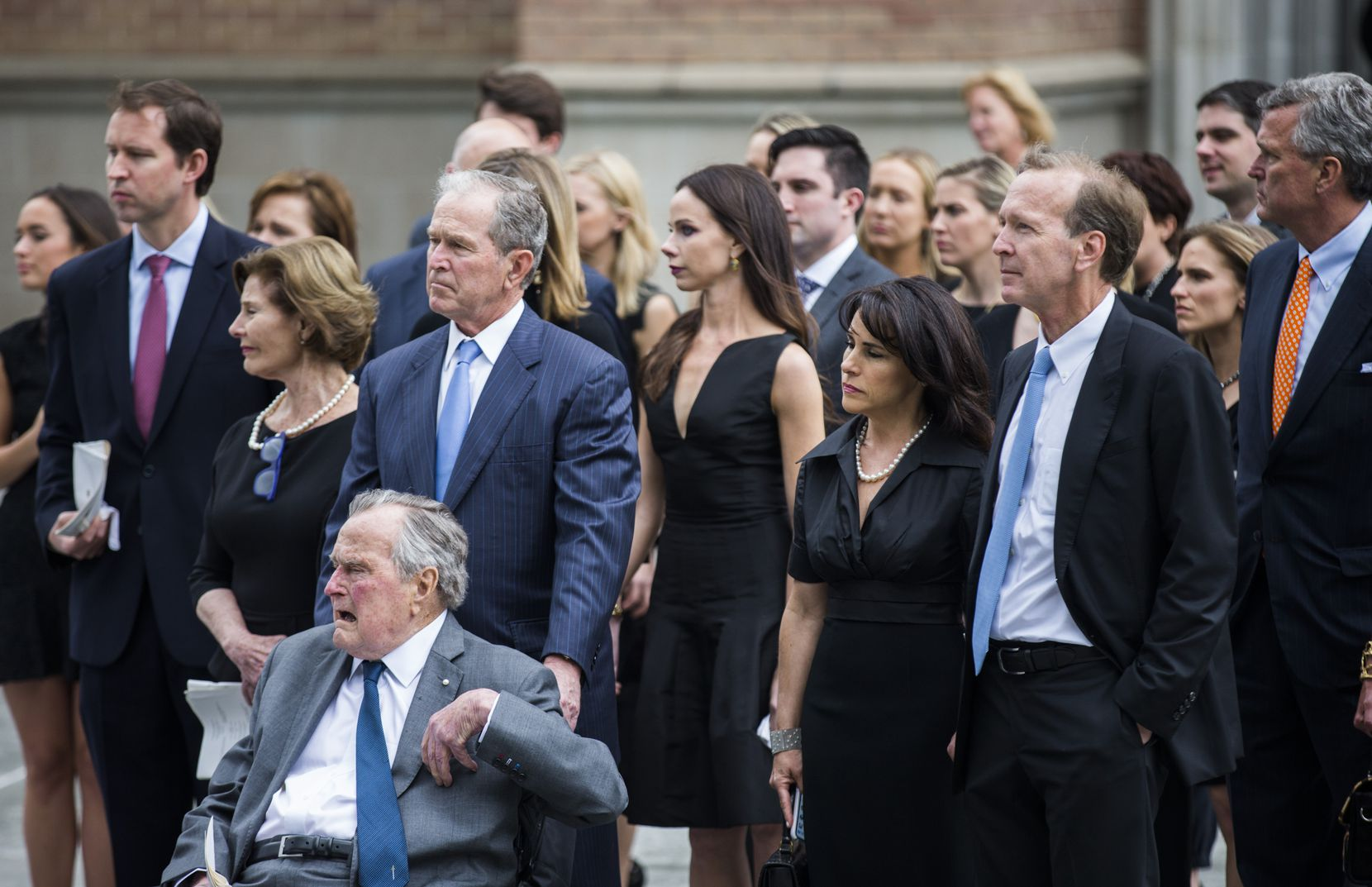 Former President George W. Bush escorts his father, former President George H.W. Bush, out of St. Martin's Episcopal Church in Houston. They had attended the funeral for former first lady Barbara Bush with family members including former first lady Laura Bush.
