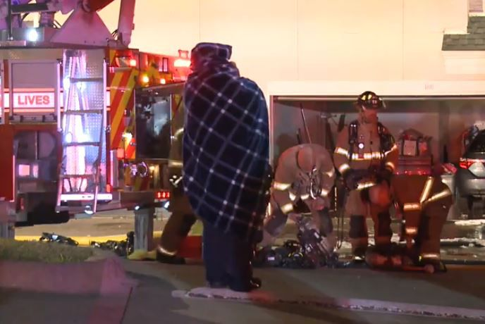 A resident wrapped in a blanket to ward off the cold watches as Plano firefighters battle an apartment blaze Monday night.