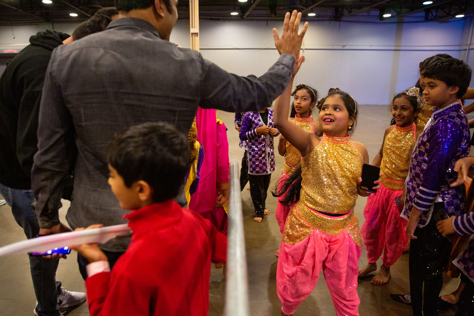 Balayashmitha Allada gets a high-five Saturday after performing with her troupe from Nrithya Dance Academy at Fair Park in Dallas.