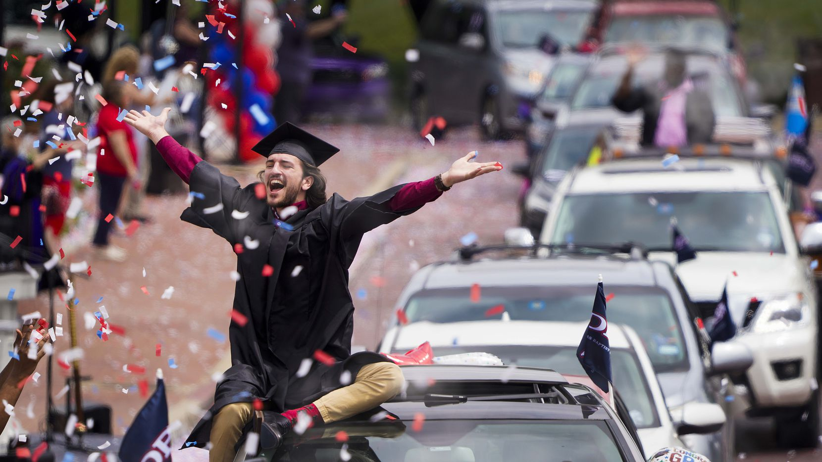 Graduate William Santini celebrated amid raining confetti in a commencement parade at Dallas Baptist University in May. Students heard their names called as they passed Pilgrim Chapel before proceeding to receive their degrees.