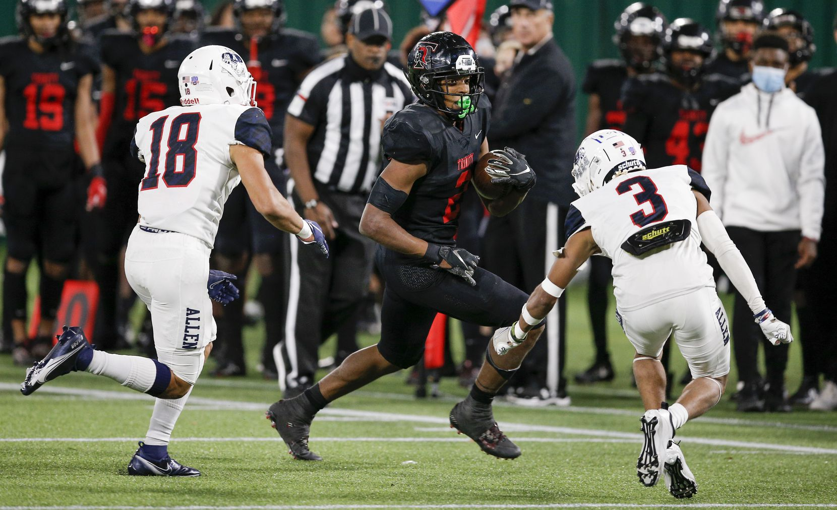 Euless Trinity junior running back Ollie Gordon (2) looks for room against Allen senior defensive back Matthew Tousant (3) and sophomore defensive back Malakai Thornton (18) during the second half of a high school Class 6A Division I Region I semifinal football game at Globe Life Park in Arlington, Saturday, December 26, 2020. Trinity won 49-45. (Brandon Wade/Special Contributor)