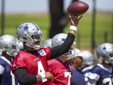 Dallas Cowboys quarterback Dak Prescott tosses a ball with his left, no-throwing, arm during a practice at training camp on Tuesday, Aug. 3, 2021, in Oxnard, Calif.