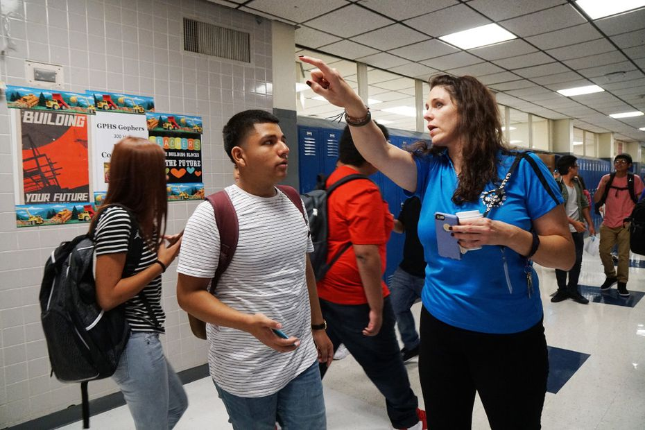Freshman Bryan Sandoval gets directions to class from Campus Life Coordinator Jalah Grey on the first day of school at Grand Prairie High School. The faculty is carrying on in the absence of Lorimer Arendse, the school's principal, who is battling lung cancer.