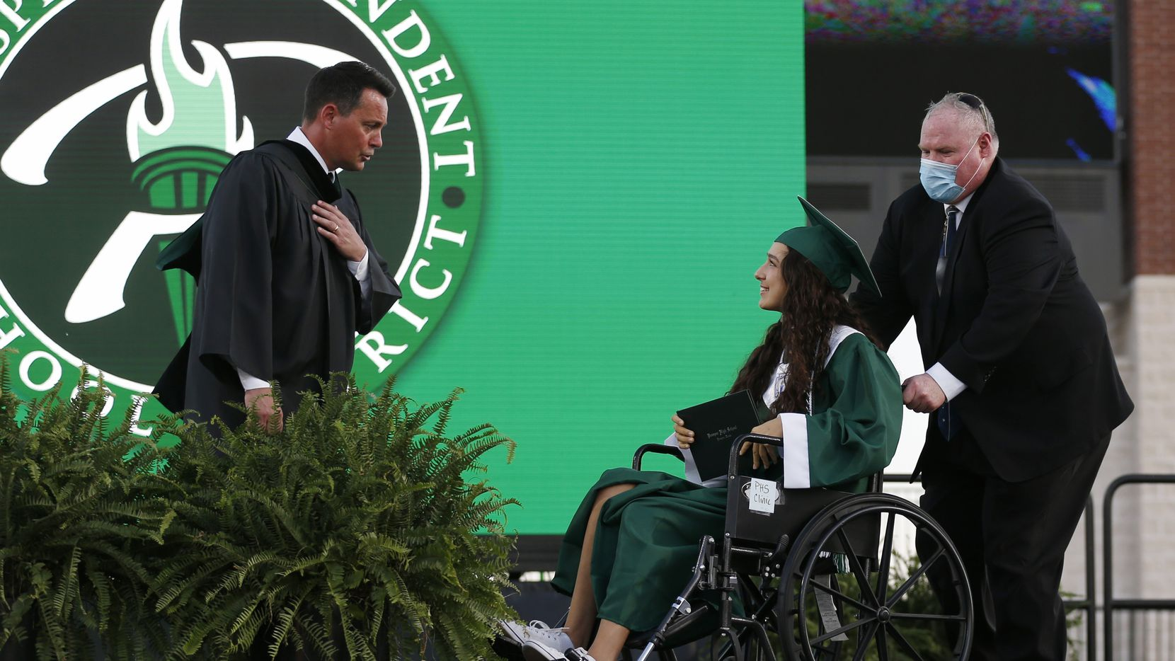 Prosper High School principal, Dr. John M. Burdett talks to Prosper High School softball player Lexie Bell as she is pushed on the stage by Prosper softball coach Todd Rainwater after she received her diploma during Prosper High School's graduation ceremony at Children's Health Stadium in Prosper, Texas on Friday, June 5, 2020. Bell signed to play softball at St. Edward's University. But she was recently diagnosed with Ewing Sarcoma, a rare form of cancer.