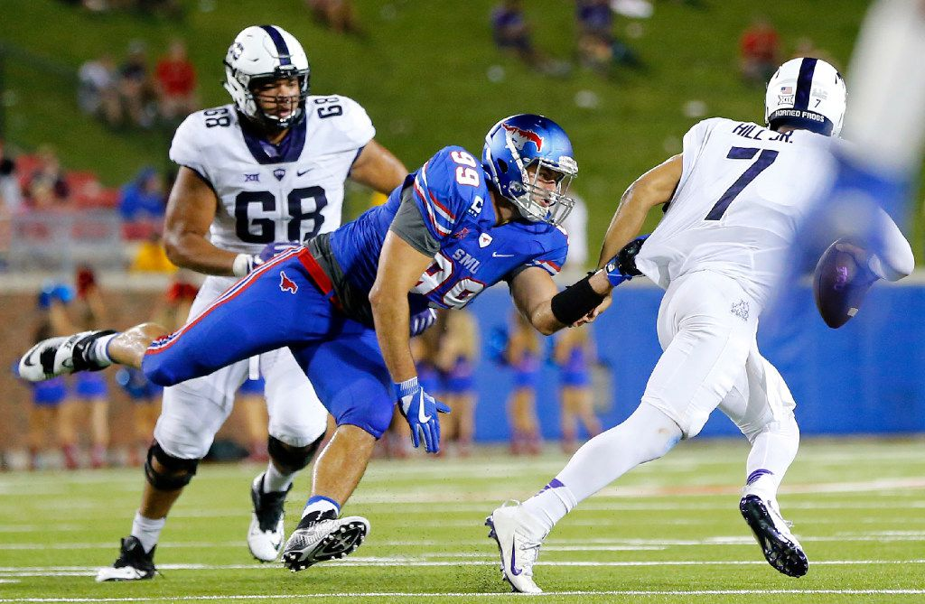 Southern Methodist Mustangs defensive end Justin Lawler (99) tries to hang on to TCU Horned Frogs quarterback Kenny Hill (7) in the fourth quarter at Gerald J. Ford Stadium in University Park, Texas, Friday, September 23, 2016. TCU won the Battle of the Skillet, 33-3. (Tom Fox/The Dallas Morning News)