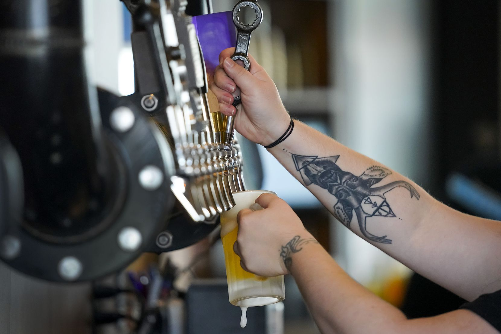 Stephanie Welch fills a beer at Thunderbird Station, which opened Sept. 17, 2020 in Deep Ellum.