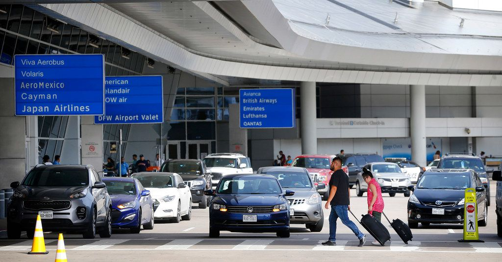 Airline passengers walk the drop-off and pick up area at Dallas-Fort Worth International Airport's Terminal D.