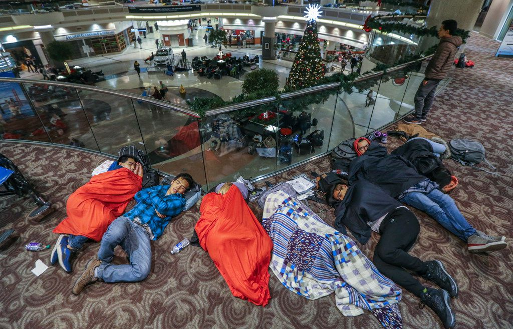 Travelers slept in the atrium at Hartsfield-Jackson International Airport on Monday, the day after a massive power outage brought operations to a halt. (John Spink/The Associated Press)