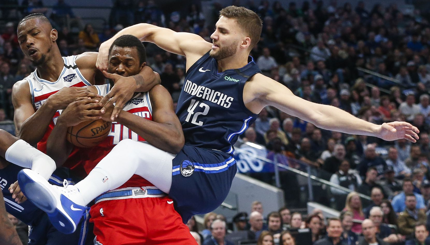 Mavericks forward Maxi Kleber tangled with Sacramento's Harry Giles III (left) and former Maverick Harrison Barnes while going for a rebound in February at American Airlines Center. Four weeks later, the season was shut down for over four months.