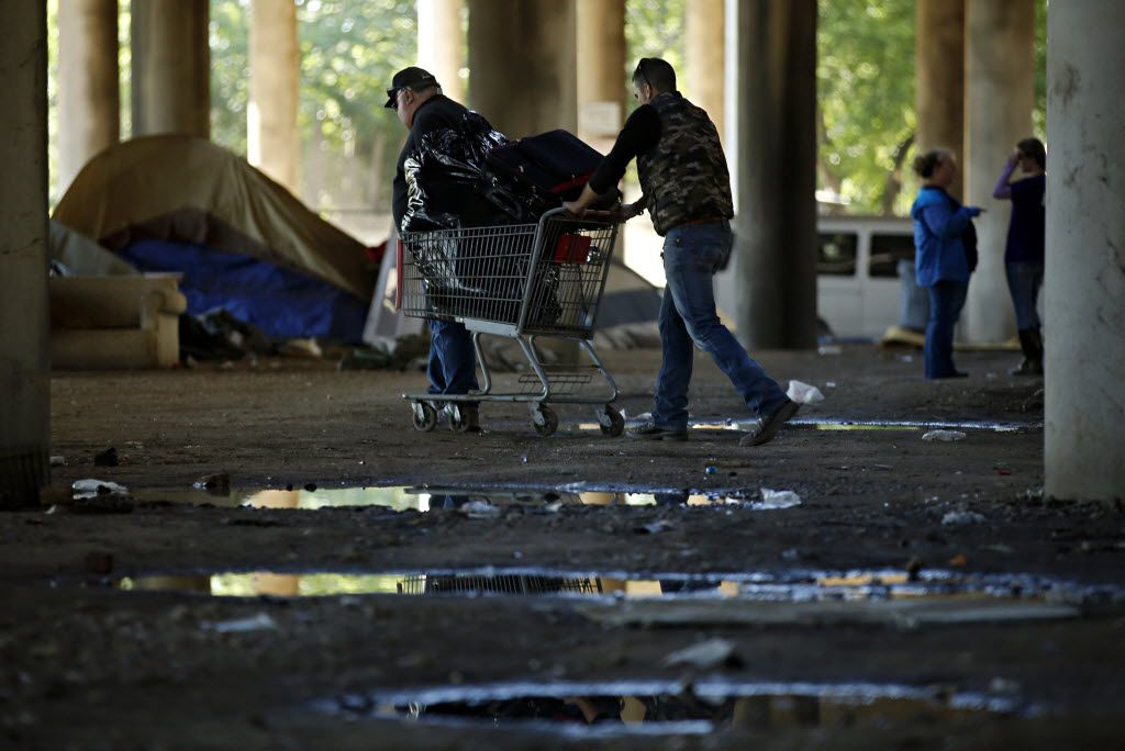 Men push a shopping cart full of belongings in Tent City Tuesday, May 3, 2016 in Dallas. The final two sections of the contentious homeless encampment where closed Tuesday morning, sending the remaining residents scrambling for shelter.