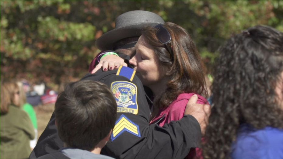 Nicole Hockley, mother of Sandy Hook victim Dylan, hugs first responder Sgt. William Cario after the Sandy Hook Elementary School shooting in 2012. Hockley discusses the lost of her son in Newtown.
