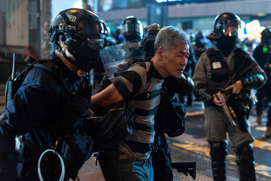 A man is escorted by the police after a pro-democracy rally in the Mong Kok district in Hong Kong on October 27, 2019. Police fired tear gas and rubber bullets at protesters who defied authorities to hold a rally on Hong Kong's scenic harbor front, another flashpoint in months of political unrest gripping the city.