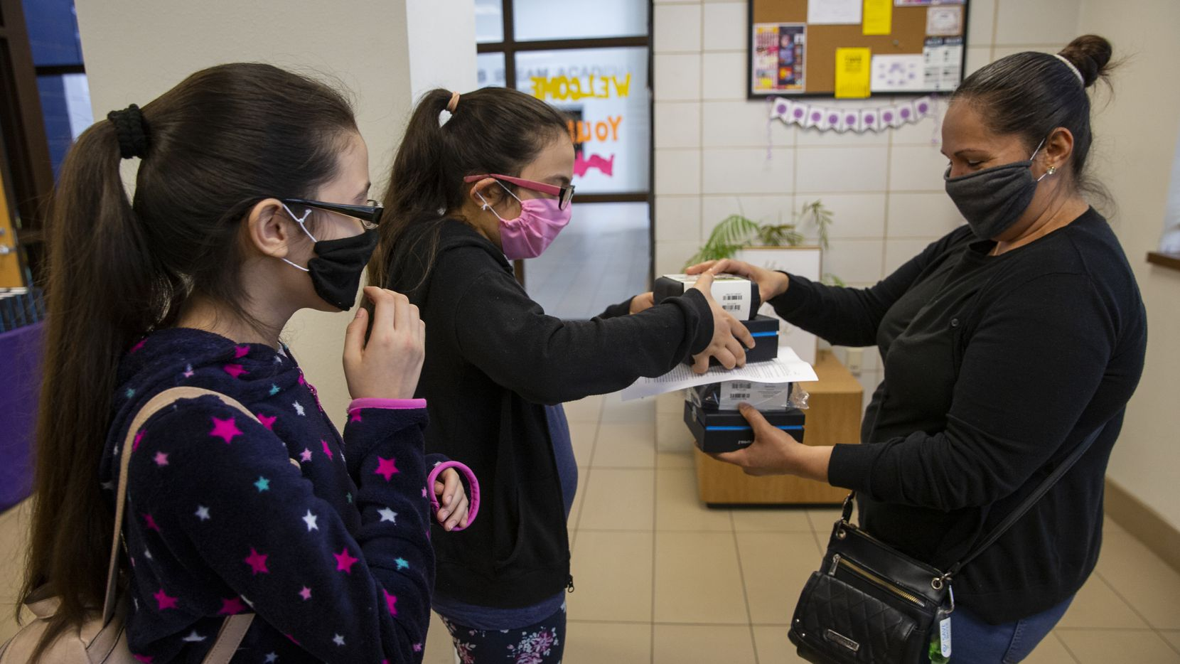 (From left) Adlemi Morales, 13, and Emeline Morales, 11, grab WiFi hotspots provided by DISD from their mom Imelda Tinajero at Young Women's STEAM Academy at Balch Springs on April 24, 2020 in Dallas. The girls were using their neighbors WIFI to complete homework.