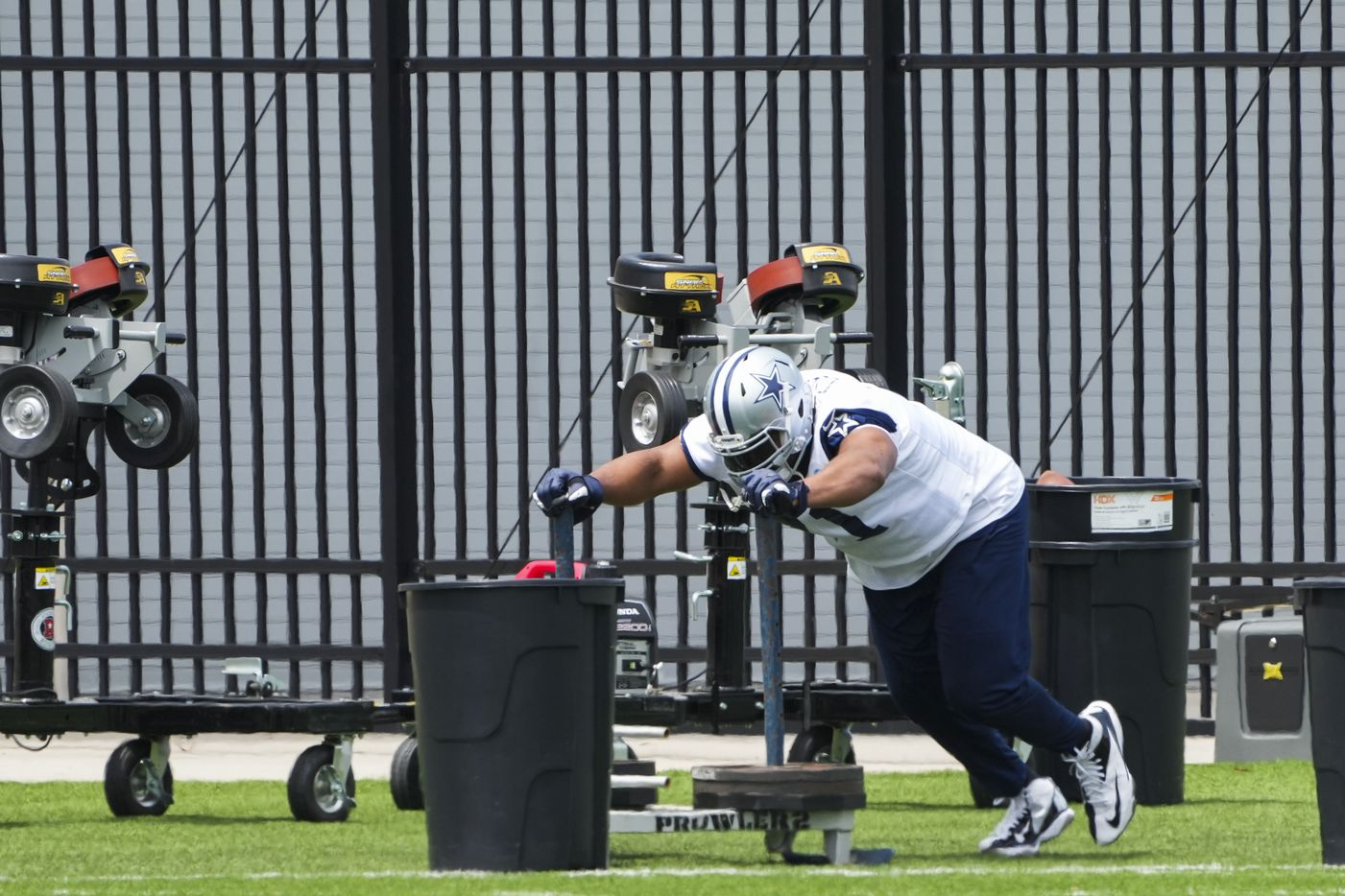 Dallas Cowboys tackle La'el Collins pushes a weighted sled during a minicamp practice at The Star on Tuesday, June 8, 2021, in Frisco. (Smiley N. Pool/The Dallas Morning News)