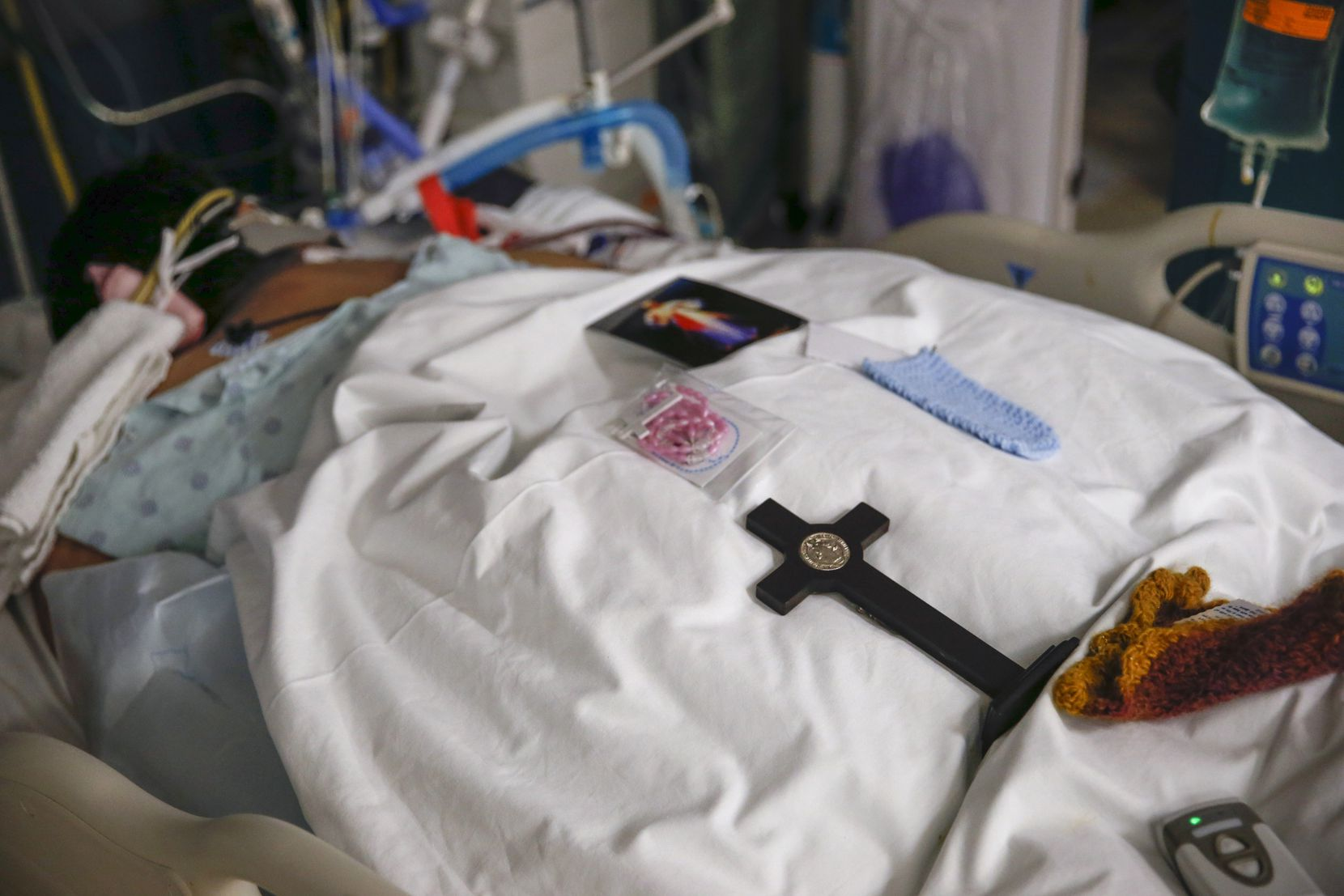 A cross, rosary and prayer card provided by a patient's family rest on the person's blanketed back.